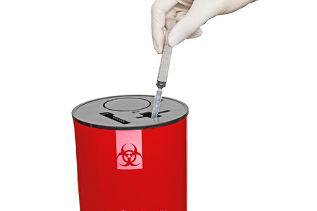 Doctor put syringe in red disposal boxes on white background