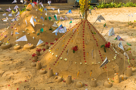 Prayer flags , pagoda and flower on sand in Songkran day festival , Thailand.