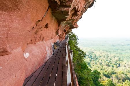 plentifully: Beautiful Wooden bridge in red cliffside at Wat Phu tok mountain. Bueng Kan Thailand