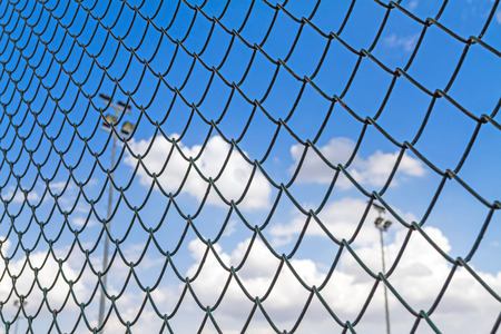 Blue sky behind the barbed wire  fence with sport light photo