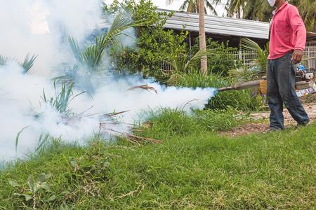 dengue: L'uomo appannamento per prevenire la diffusione della febbre dengue in Thailandia Archivio Fotografico