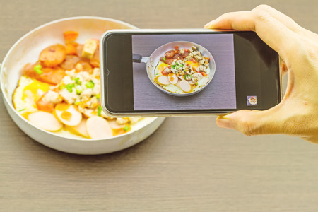 indochina: Hand of girl taking pictures on a mobile phone in Indochina pan-fried egg with toppings tomatoes , chili ,pepper , chili sauce , bacon , pork   served with roasted breads for breakfast  on black wooden