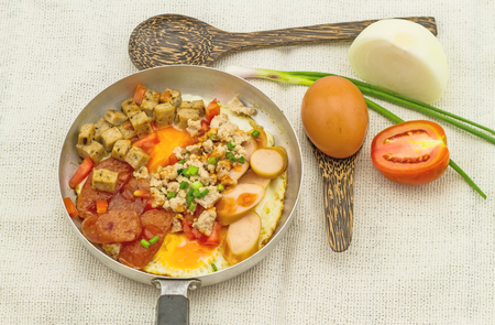 indochina: Indochina pan-fried egg with garnish tomatoes , chili ,pepper , chili sauce , bacon , pork ,onion ,   on white sack fabric Stock Photo