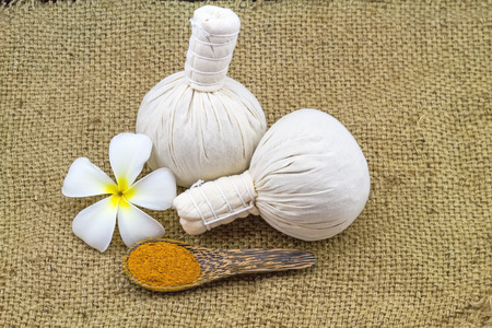 spp: Spa herbal compressing ball , white frangipani flowers Plumeria spp , Apocynaceae, Pagoda tree, Temple tree and turmeric powder  in wooden spoon on brown sack fabric background
