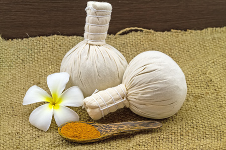 apocynaceae: Spa herbal compressing ball , white frangipani flowers Plumeria spp , Apocynaceae, Pagoda tree, Temple tree and turmeric powder  in wooden spoon on brown sack fabric background