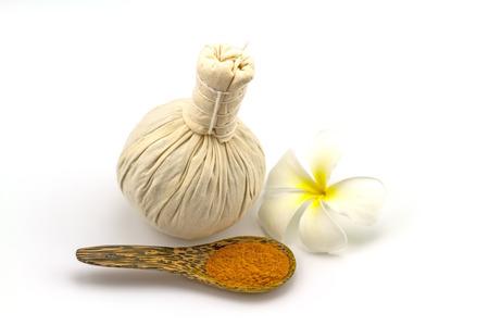 masajes relajacion: Spa a base de hierbas bola de compresi�n, flores blancas frangipani Plumeria spp, Apocynaceae, �rbol de pagoda, templo �rbol y polvo de c�rcuma en una cuchara de madera sobre fondo blanco