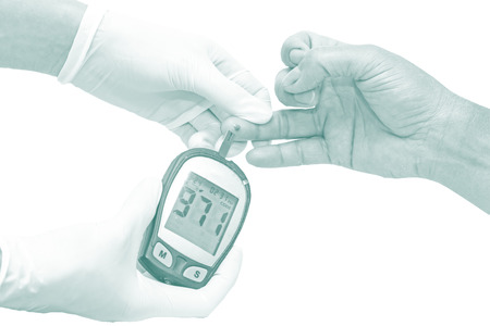 blood glucose meter: blood glucose meter, the blood sugar value is measured on a finger by  female doctor in white medical gloves in blue tone Stock Photo