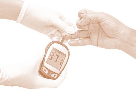 blood glucose meter: blood glucose meter, the blood sugar value is measured on a finger by  female doctor in white medical gloves in brown tone