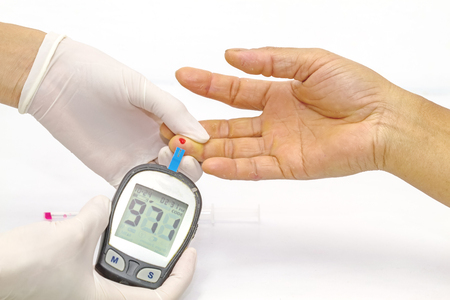 diabetes mellitus: blood glucose meter, the blood sugar value is measured on a finger by  female doctor in white medical gloves