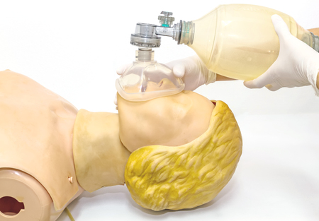 reanimate: Hand and white medical gloves of doctor demonstration resuscitation CPR Technique by mask with bag on model