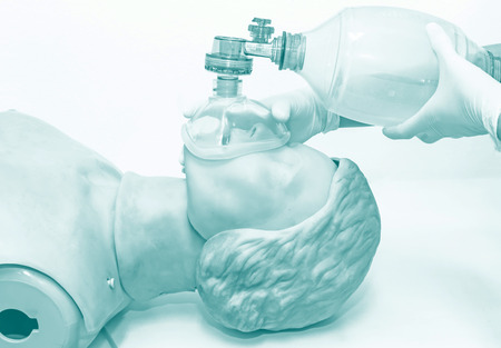 revive: Hand and white medical gloves of doctor demonstration resuscitation CPR Technique by mask with bag on model in blue tone