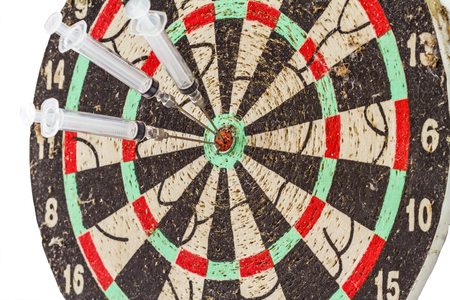 bull's eye: Glass syringe and needle as darts arrows in the target center bulls eye Stock Photo