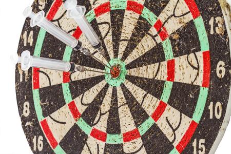 bulls eye: Glass syringe and needle as darts arrows in the target center bulls eye Stock Photo