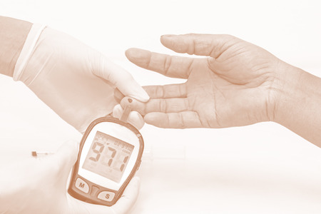 hyperglycemia: blood glucose meter, the blood sugar value is measured on a finger by  female doctor in white medical gloves