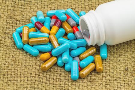 pastillas: pastillas de colores y las tabletas de botellas blancas en saco marrón fondo de la tela