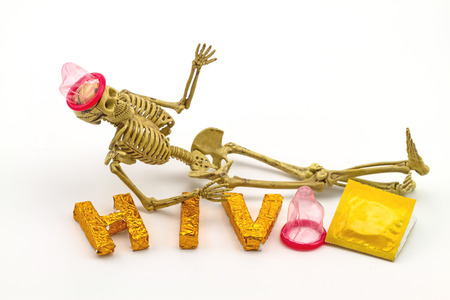 condoms: Still  life concept human body bone  wear condoms  and  A word HIV  on white background indicate danger of AIDS Stock Photo