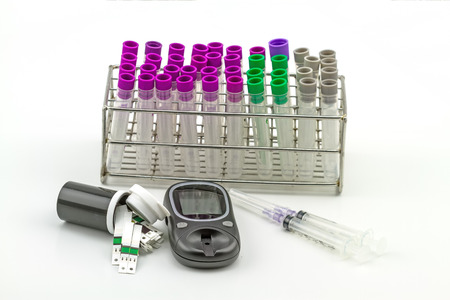 Medical Blood tube, test tube for laboratory empty on  rack and disposable syringe , glucose strips test  on a while background Stock Photo