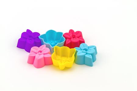 silhouette fleur: Colorful des moules en silicone pour la cuisson sous la forme de coeurs, objet sur un fond blanc