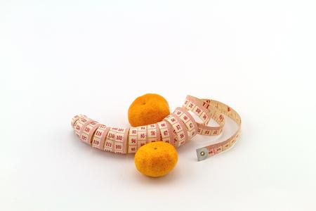 pene: Manzana Naranja madura con rosa forma de medición de cinta como el pene en el fondo blanco