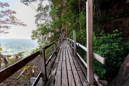 plentifully: Beautiful Wooden bridge in red cliffside at Wat Phu tok mountain. Bueng Kan, Thailand