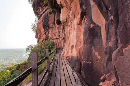 dwell: Beautiful Wooden bridge in red cliffside at Wat Phu tok mountain. Bueng Kan, Thailand