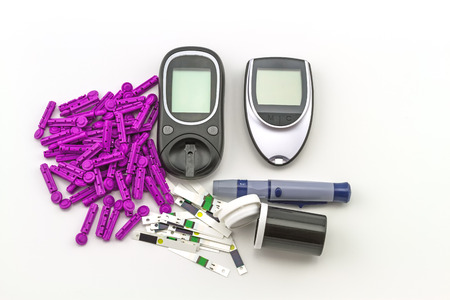 blood glucose meter: blood glucose meter, the blood sugar value is measured on a finger on white background. Stock Photo