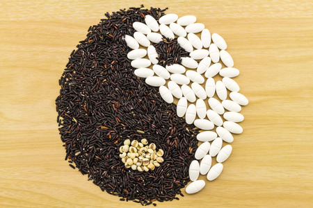 indicate: Black rice and white pill  forming a yin yang symbol on brown wooden indicate blending of herb and medicine Stock Photo