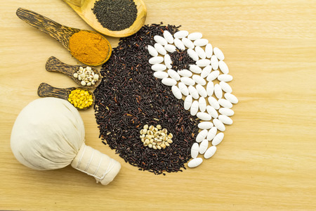 indicate: Black rice and white pill  forming a yin yang symbol  and Spa herbal compressing ball , turmeric powder , millet , soybean , basil seed in wooden spoon  on brown wooden indicate blending of herb and medicine