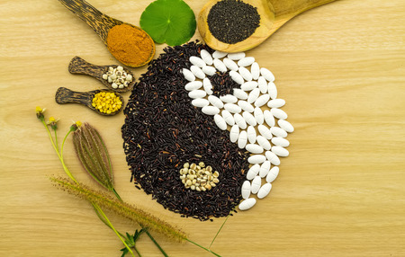 Black rice and white pill  forming a yin yang symbol  and turmeric powder , millet , soybean , basil seed in wooden spoon  on brown wooden indicate blending of herb and medicine