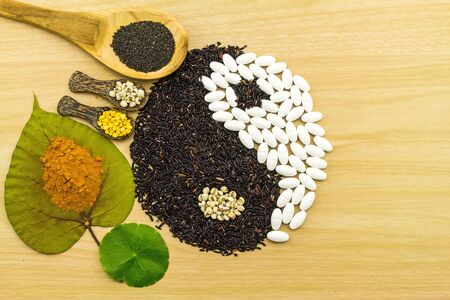 yin: Black rice and white pill  forming a yin yang symbol  and Spa herbal compressing ball , turmeric powder , millet , soybean , basil seed in wooden spoon  on brown wooden indicate blending of herb and medicine