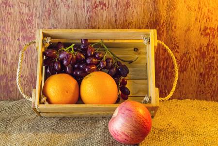 sisal: Fruits apple, orange , grape   in an wood box, on sack sisal background