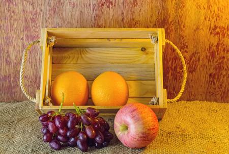 apple sack: Fruits apple, orange , grape   in an wood box, on sack sisal background