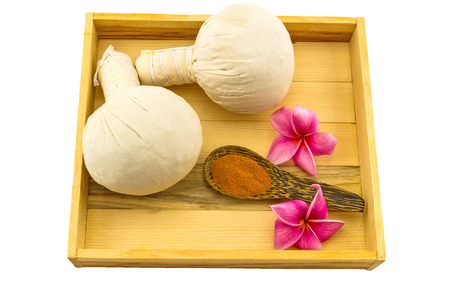 apocynaceae: Spa herbal compressing ball , pink frangipani flowers Plumeria spp , Apocynaceae, Pagoda tree, Temple tree and turmeric powder in wooden spoon and wooden box isolate on white background Stock Photo