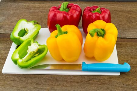 colorful still life: still - life concept colorful sweet bell pepper capsicum  and blue knife in white block   on wooden background Stock Photo