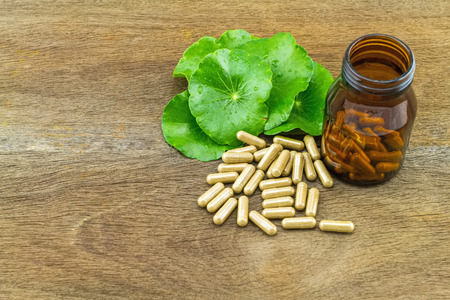 longevity drugs: Green Asiatic Pennywort Centella asiatica  and black bottle pill capsules on wooden  background