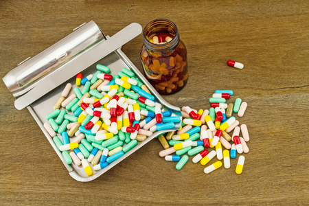 dispense: Colorful tablets medicine in the drug counting tray and black bottle on wooden  background Stock Photo