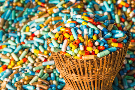 expire: Many colorful medicines expire in bamboo weave basket  package  on cement floor,soft focus Stock Photo