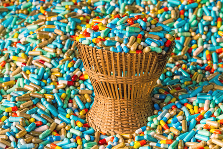 expire: Many colorful medicines expire in bamboo weave basket  package  on cement floor Stock Photo