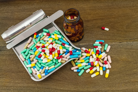dispense: Colorful tablets medicine in the drug counting tray and black bottle on wooden background