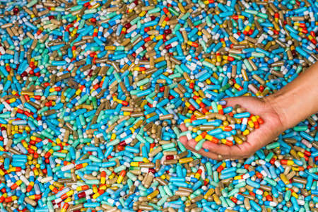 expire: Hand of man show many colorful medicines expire on cement floor
