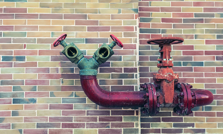 pipe line: Red pipe line with brown valve on colorful brick wall