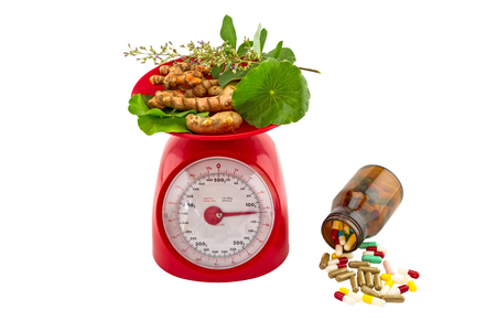 trifolia: Assorted of herbal  in red weight scale and colorful pills in black bottle on white background Stock Photo
