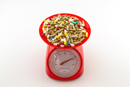 medicate: Colorful pills in red weight scale on  white background
