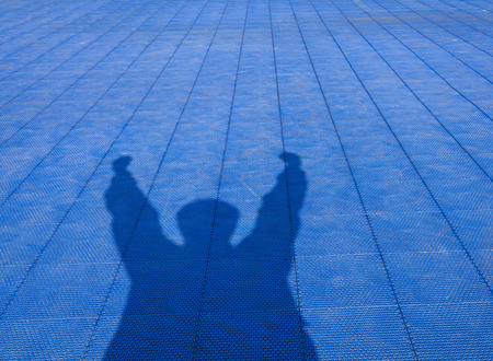 Shadow Of Man Who Show Extend The Arms On Blue Rubber Flooring Futsal Field Background