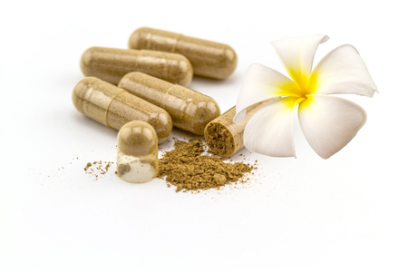 Herbal capsule and white and yellow Plumeria spp. flower(frangipani , Pagoda tree or Temple tree ) on white background. Stock Photo