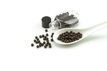 bolus: Black pills of traditional medicine or Black bolus near bottle  and white ceramic spoon on white background.