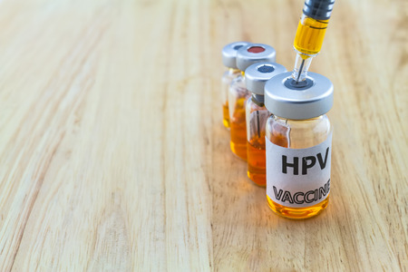 Bottle vaccine of Human papillomavirus (HPV) vaccine and disposable syringe on wooden background Banco de Imagens