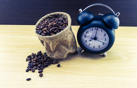 sisal: vintage classic alarm clock and coffee beans in sack sisal on wooden table