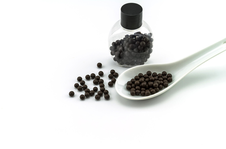 Black pills of traditional medicine or Black bolus near bottle  and white ceramic spoon on white background.