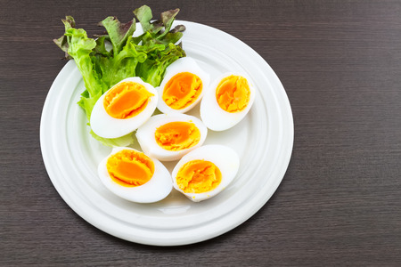 duck egg: Close up medium soft boiled duck egg portion and green salad in white dish on black wooden background. Stock Photo